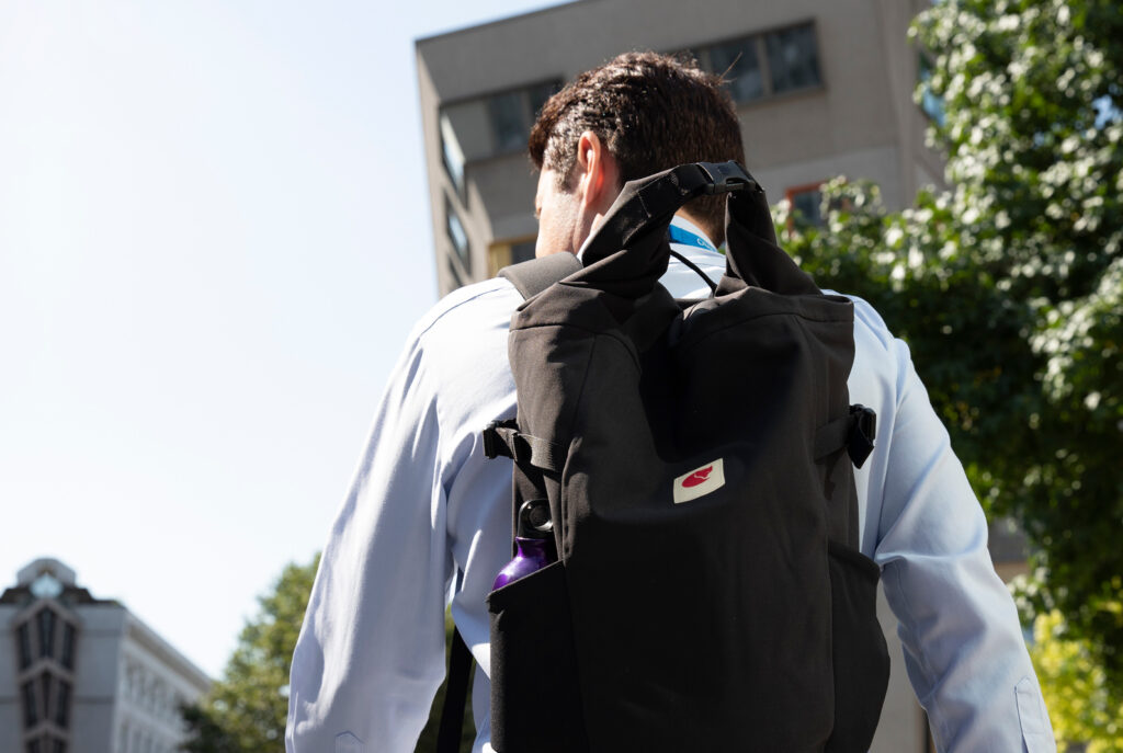 Image of a man with a backpack walking away.  He's in a city, there are office blocks in the background.