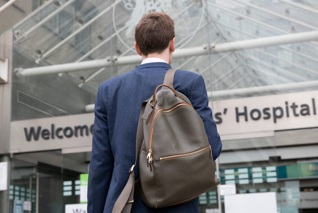 Image of a person with a hospital in the background