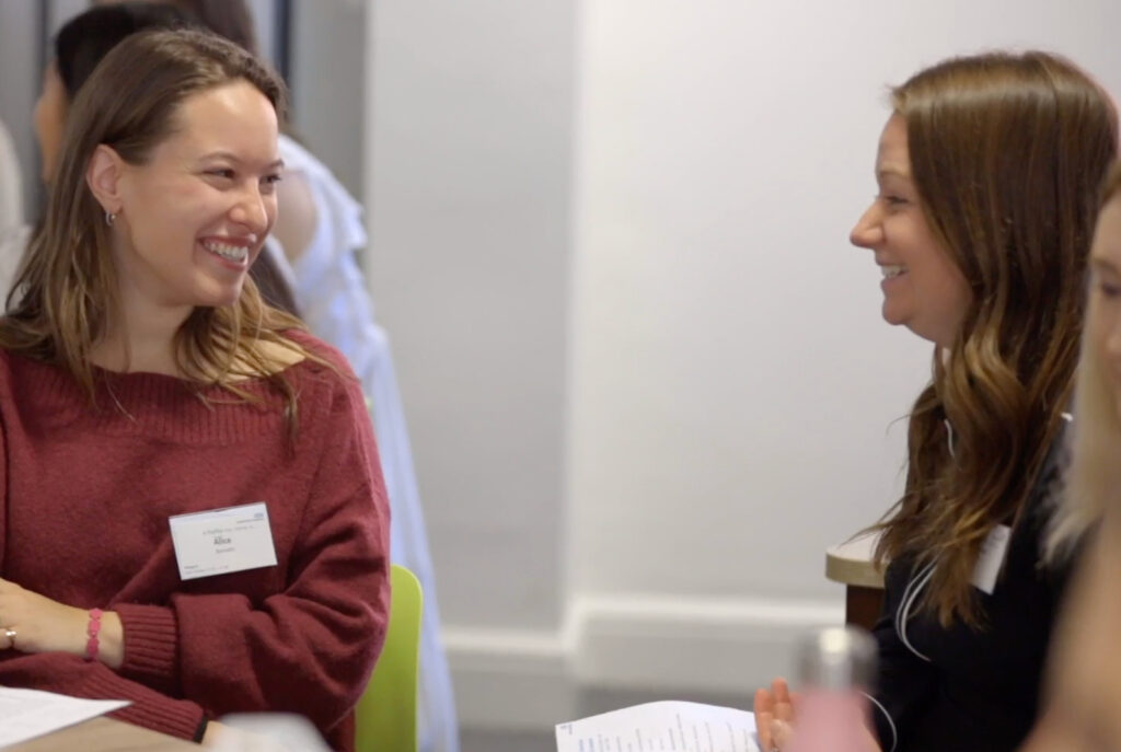 Image of two women talking and smiling, in a work setting.