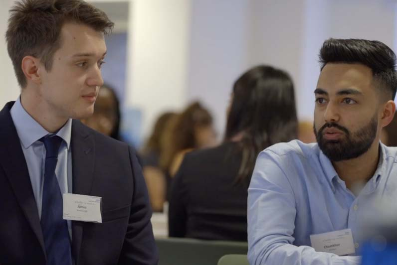 Image of two men talking in a work setting
